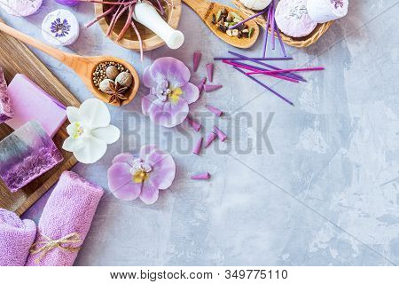 Top View Of Violet Purple Set For Relaxing Spa Treatments. Wooden Mortar Pounder With Herbs, Spoons