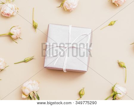 Women Day Present. Silver Gift Box. Pink Roses Decorative Arrangement On Pale Peach Background.
