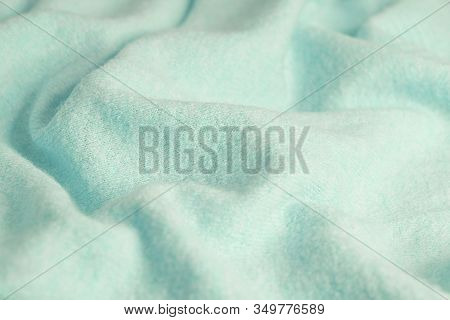 Soft Knitted Fabric Made Of Cashmere With Large Folds, A Detail Of Clothes. Blue Fabric Texture