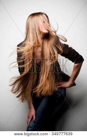 Girl Dressed In Black Jacket, With Long Flowing Hair, Posing With Her Head Turned To Side Against Wh