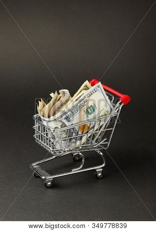 One Miniature Shopping Cart Filled With Us Dollar Banknotes Against A Dark Background.