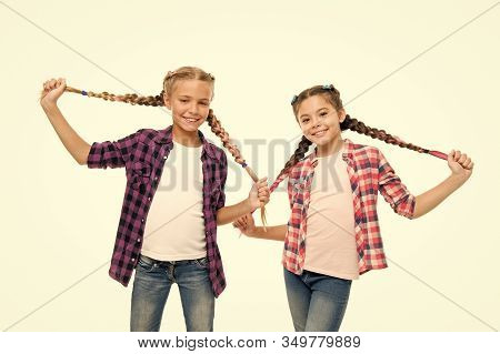 Doing Cute And Easy Hair Style. Happy Children Hold Long Braided Hair Style. Small Girls Smile In Ca