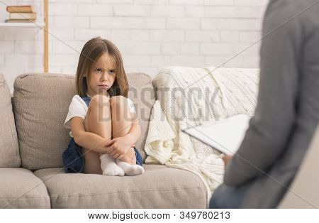 Child Counseling Concept. Concerned Little Girl At Therapy Session With Children Psychologist Sittin