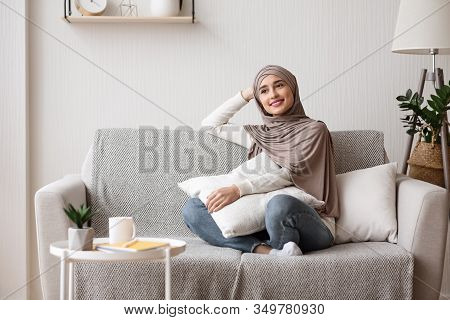 Daydreaming. Relaxed Arabic Girl In Hijab Sitting On Sofa In Stylish Interior, Thinking About Someth
