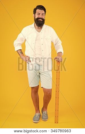 Back To Class Is Here. Happy Hipster Holding Ruler On Yellow Background. Brutal Hipster Smiling Befo