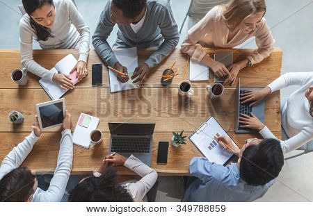 Office Lifestyle Concept. Top View Of International Young Business Team Having Meeting At Office, Si