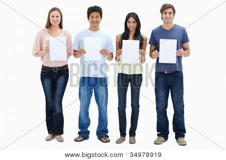 Four people in jeans holding four signs against white background