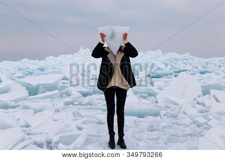 Girl Covering Her Face With Triangle Block Of Ice Staying On Hummock In Frozen Lake Kapchagai Near A