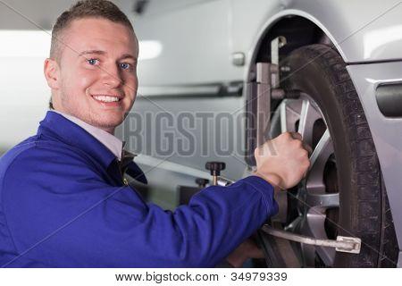 Mechanic changing a car wheel in a garage