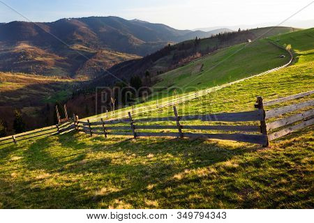 Small Old Wooden Fence Located On Green Hill. On Background Mountains And Clear Blue Sky Without Clo