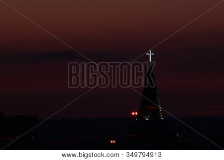 Glowing Cross On The Spire Of A Babtist Church At Dusk Against A Sunset Crimson Sky Over The Horizon