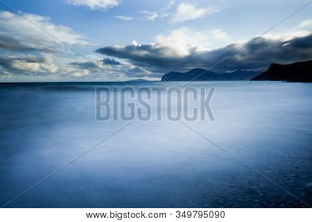 Calm Ocean Covered In Fog, Over Bright Sky With Clouds. Mountains In The Distance To The Right