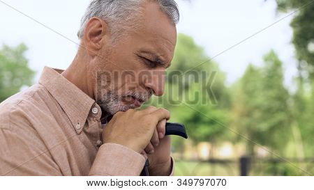 Thoughtful Retired Man With Walking Stick In Park, Social Security, Pension Age