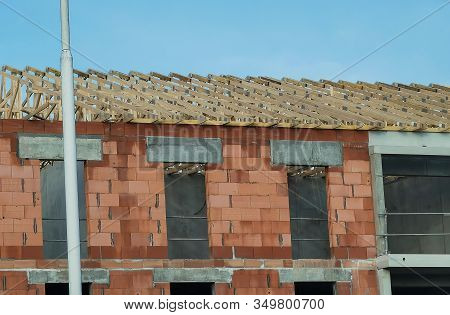 Unfinished Brick House, Building Under Construction And Wooden Roof Frame