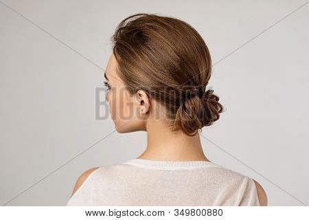Cute Woman With Beautiful Elegant Hair Bun On Gray Background