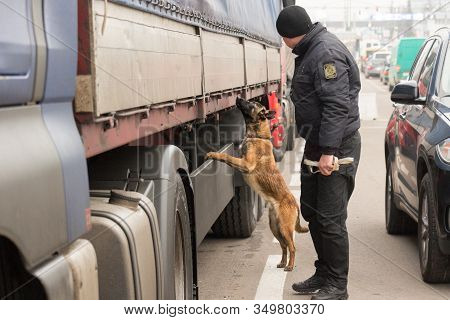 Shegini, Ukraine - November, 2018: Ukrainian Border Guard With A Service Dog Inspects Vehicles At Th
