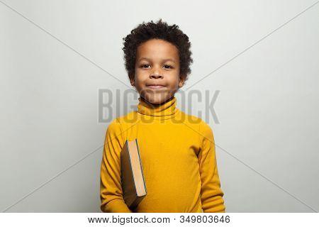 Cute African American Kid Boy Student Holding Book On White Background. Black Kid School Boy Portrai