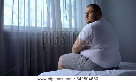 Sad Fat Man Sitting On Bed At Home, Looking At Camera, Depression, Insecurities