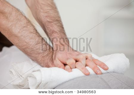 Close-up of a masseur massing a woman indoors poster