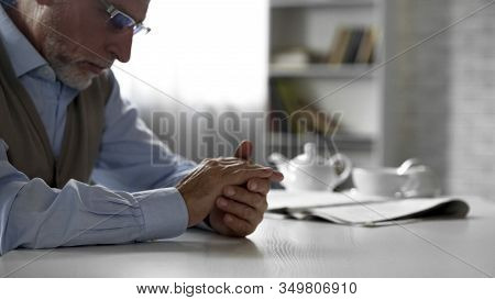 Retiree Man Sitting At Table And Looking At His Hands, Feeling Depressed