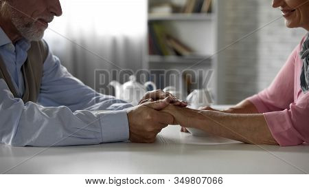 Retiree Husband Holding Tenderly Wifes Hand, Having Tea Together, Happiness