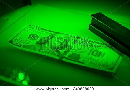 Verifying The Authenticity Of The Hundred Dollar Bill In Ultraviolet, Orange, Malachite, Emerald And