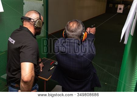 Shooting In The Dash Of Short-barreled Weapons. A Man Aims At A Target Before Firing A Pistol. The I