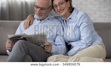 Retiree Man Reading Newspaper, Wife Putting Arm Around His Shoulders, Marriage