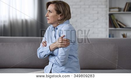 Worried Elderly Female Sitting On Couch, Feeling Anxious, Psychological Problems
