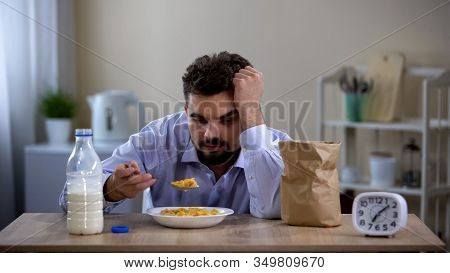 Tired Young Lonely Man Eating Unhealthy Sugary Corn Flakes For Breakfast