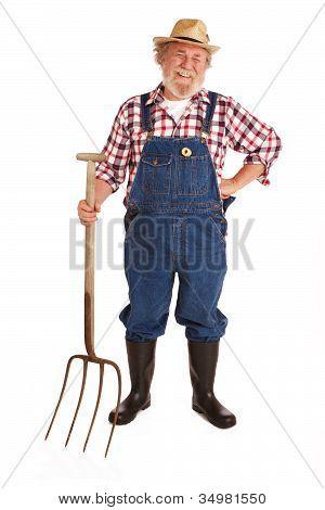 Happy Senior Farmer Holding Hay Fork