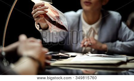 Female Prosecutor Showing Knife With Blood To Suspect, Waiting For Confession