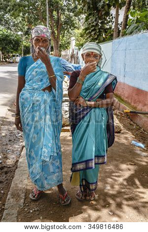 Bengaluru, India - October 24, 2012. Two Indian Women Dressed In Saris Drink Tea Whilst On A Break F