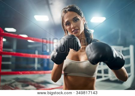 Front View Of Fit Smiling Brunette Woman Wearing Boxing Gloves And Beige Top. Young Attractive Fight