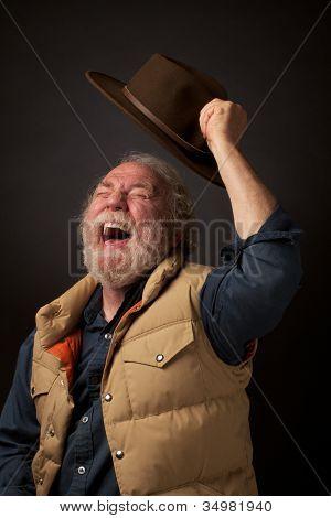 Joyful senior man waves his hat in the air