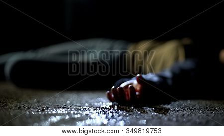 Close-up Bloody Body Of Young Woman Lying On Ground, Terrible Killing, Robbery