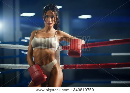 Portrait Of Pretty Slim Brunette Woman Wearing Red Boxing Gloves, Underwear And Leaning On Rope. Fro