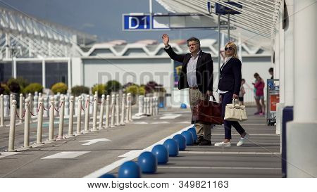 Middle-aged Male And Female Leaving Airport And Hailing Taxi, Traveling