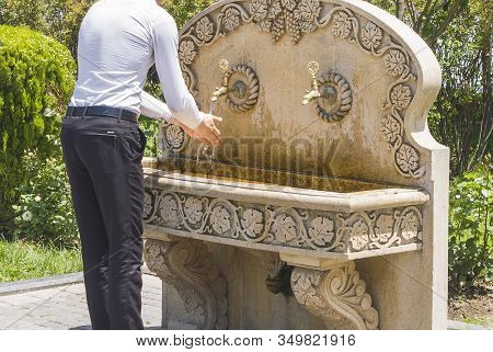 A Man Washes His Hands Under A Tap With Free Water Installed In A City Park. Tap With Free Water In