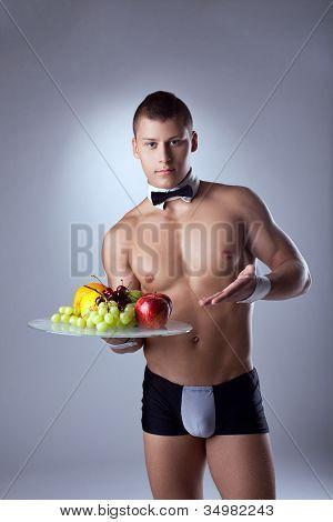 muscular man waiter offer fruits