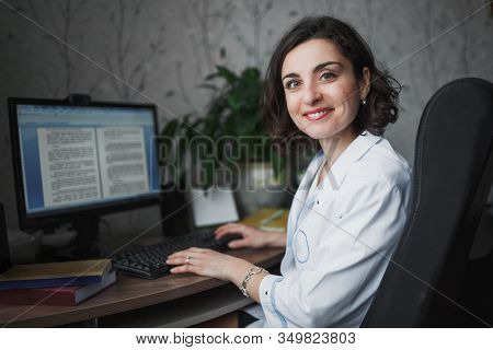 Smiling Woman Doctor In A With Dark Curly Hair In White Medical Robe Sitting At A Table With Books,