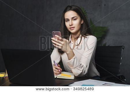Female Executive Sitting At Desk In Office, Using Portable Digital Devices For Work. Girl Typing On