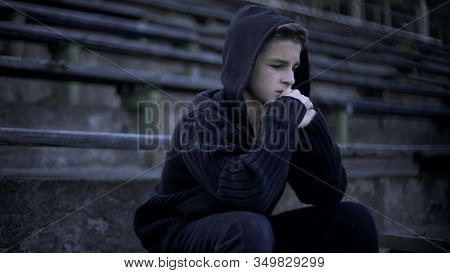 Upset Boy Sitting On Stadium Tribune, Feels Depression, Loneliness And Sorrow