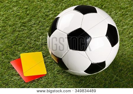 Soccer Ball With Referee Yellow And Red Cards On Grass Background - Penalty, Foul Or Sports Concept,