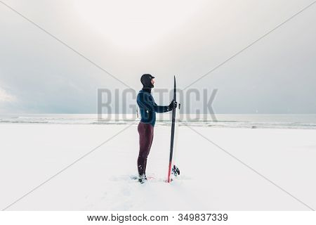 Cold Winter And Surfer With Surfboard. Snowy Day With Surfer In Wetsuit.