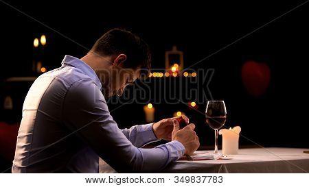 Hopeless Man Holding Engagement Ring, Sitting In Restaurant Alone, Break Up