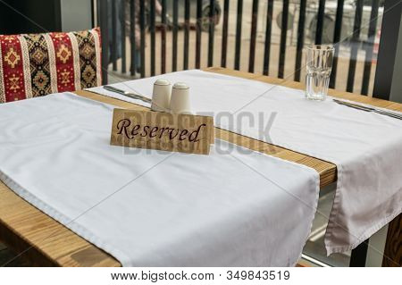 The Plate Is Reserved On A Table With White Tablecloths In A Cafe Or Restaurant. Table Setting.