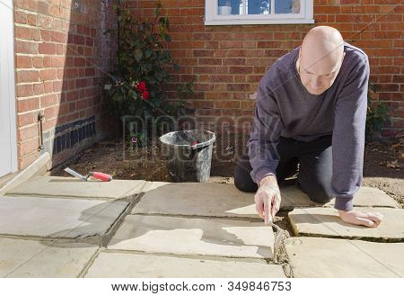 Builder Laying And Grouting York Stone Paving Slabs Outdoors, Diy Home Patio Project , Uk