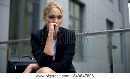 Anxious Woman Sitting On Bench, Worried About Dismissal From Work, Depression