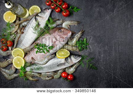 Fresh Raw Fish Of Sea Bream, Sea Bass And Shrimp With Lemon, Herbs, Olive Oil, On A Dark Stone Backg